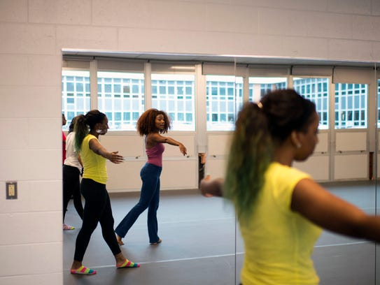 A student (front) receives instruction from dance teacher