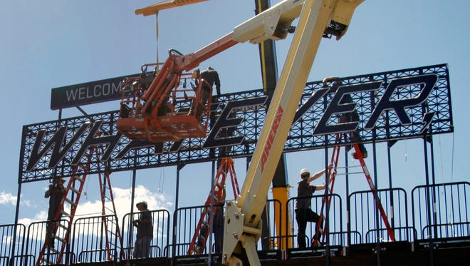 In this Wednesday, Sept. 3, 2014 photo workers install a Welcome to Whatever, USA sign across Elk Avenue, in Crested Butte, Colo. Anheuser-Busch agreed to pay $500,000 to convert the town into a set for a Bud Light commercial, a sequel to the company?s ``Up for Whatever?? Super Bowl ad that included Arnold Schwarzenegger. (AP Photo/P. Solomon Banda)
