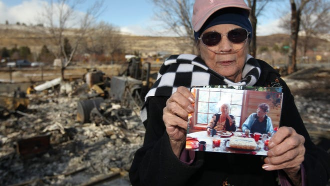 Standing in front of the rubble of her home Saturday, Jan. 21, 2012, Jeannie Watts holds a picture of herself and her mother, June Hargis, who died Thursday as a wind-driven brush fire burned through Pleasant Valley, south of Reno, Nev. Authorities confirmed that the body of Hargis, 93, was found in the fire's aftermath, but her cause of death has not been established, so it's not known if it was fire related.