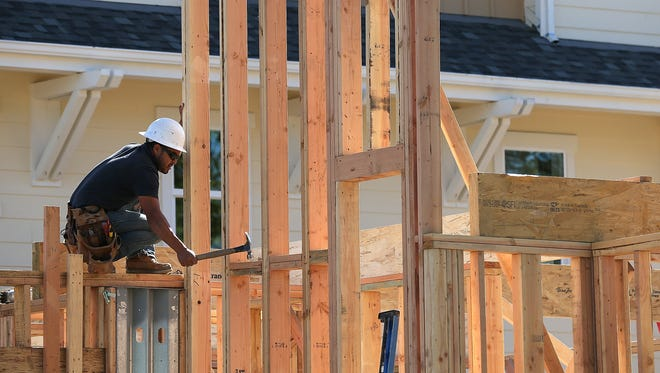 A worker hammers nails at a housing development under construction in California.