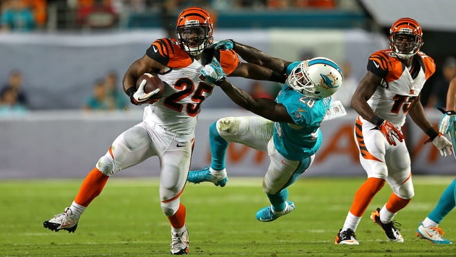 Gio Bernard is grabbed by Reshad Jones of the Miami Dolphins during a 2013 game at SunLife Stadium in Miami.