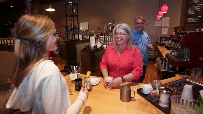 "Lea Cockrell, center, served a latte to Emily Bratton at La Grange Coffee Roasters as Chris Cockrell looked on.  The coffee shop and, the town and some nearby scenes were included in the upcoming Hallmark movie, ""The Ultimate Legacy."""
