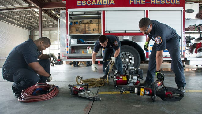 Escambia County firefighters, Otis Evans, left, Kevin Chacin, center, and Terrell Jackson, right, preform a mandatory daily systems check on an piece of equipment at Station 17 Tuesday May 10, 2016. Escambia County and the City of Pensacola are proposing to enter into a mutual aid agreement to provide overlapping fire protection to benefit the citizens of both jurisdictions.