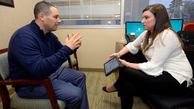Dr. Jason Dranove discuss cancer treatment guidelines with genetic counselor Stacy Lenarcic at Carolinas HealthCare System's Levine Cancer Institute on Tuesday, Dec. 13, 2016 in Charlotte, N.C. Dranove, a doctor at Levine Children's Hospital, had breast tissue removed to prevent cancer that killed his uncle. (David T. Foster III/The Charlotte Observer/TNS)