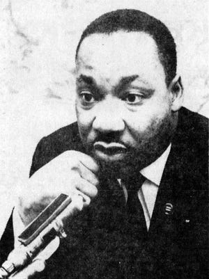 The Rev Martin Luther King Jr. listens to a reporter during a news conference at Cincinnati Gardens, May 8, 1964.