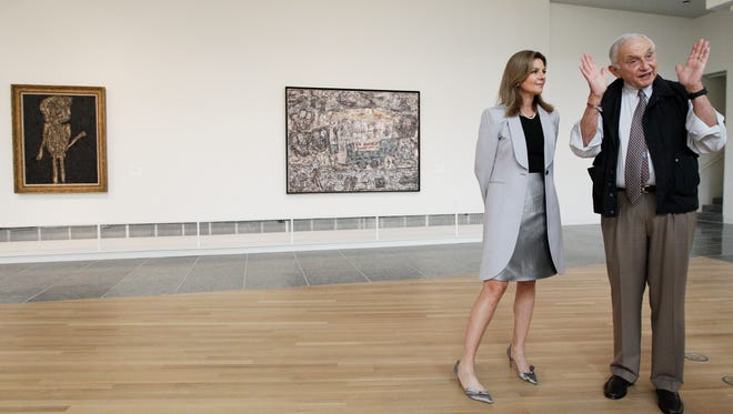 """Retail mogul Leslie Wexner, right, and his wife Abigail tour the """"Transfigurations"""" exhibit at the Wexner Center for the Arts Friday, Sept. 19, 2014, in Columbus, Ohio."""