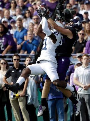 Penn State corner back Amani Oruwariye, left, intercepts a pass intended for Northwestern wide receiver Bennett Skowronek during the first half of an NCAA college football game in Evanston, Ill., Saturday, Oct. 7, 2017. Penn State won 31-7.