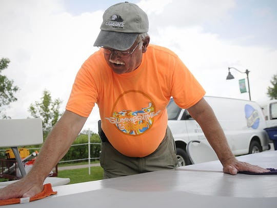 Rotary club member Mark Henry wipes down the tables in the beer garden before Summertime by George! on July 15 at Lake George. Henry thinks that the community is guests of the Rotary club and they would not welcome guests to a dirty home.