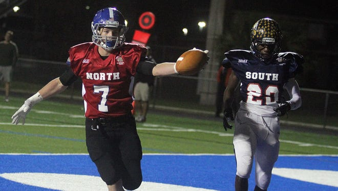 North All Star Nathan Leedy, from Barron Collier, holds the ball out after catching a touchdown pass over South defender Jules Dornevil of Naples HS in the endzone during the first half of the Naples North Rotary All-Star Football Classic Thursday night at Barron Coliier High School. Leehy scored again on another long pass late in the first half to put the North up by two TDS.