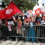A woman holds a flag with the face of opposition leader Chokri Belaid at a February rally commemorating his assassination. The Tunisian government blames Ansar al-Sharia, which Tunisian authorities and the US government consider a terrorist group, of being behind Belaid's murder.