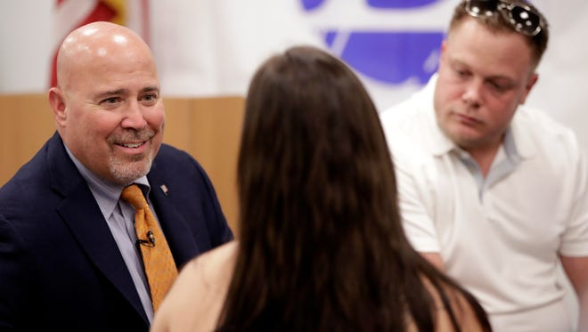 U.S. Rep. Tom MacArthur, R-N.J., left, speaks with Natalia Stathi, center, and her fiance Tim Meise during an event talking about opioid addiction at the Express Scripts mail-order pharmacy, Tuesday, July 10, 2018, in Florence, N.J. The couple works with drug addicts at a recovery house in Medford, N.J. (AP Photo/Julio Cortez)