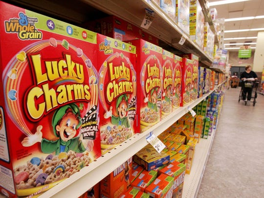 A grocery shelf of General Mills Lucky Charms cereal.