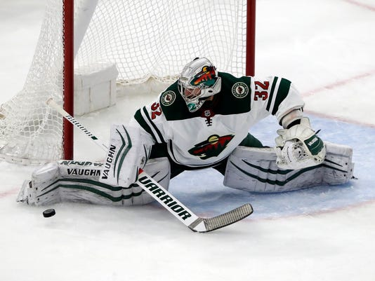 Minnesota Wild goalie Alex Stalock blocks a shot against the Chicago Blackhawks during the first period of an NHL hockey game, Sunday, Dec. 17, 2017, in Chicago. (AP Photo/Nam Y. Huh)