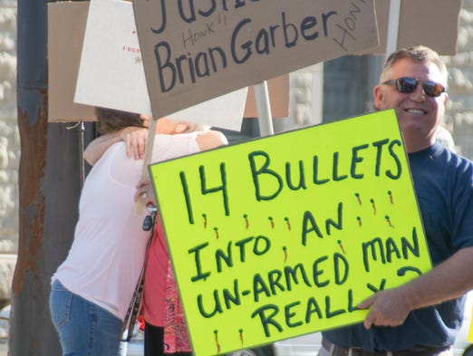 Connie Garber is hugged by a surporter whileLester Beasley, uncle of Brian Garber carries signs demanding justice for his nephew.