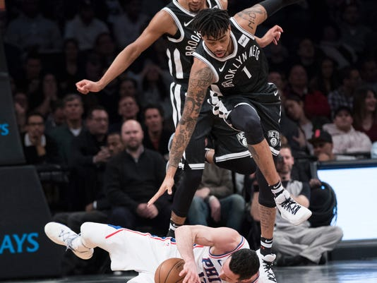 Brooklyn Nets guard D'Angelo Russell (1) and forward James Webb III jump over Philadelphia 76ers guard JJ Redick after Russell fouled Redick during the first half of an NBA basketball game, Wednesday, Jan. 31, 2018, in New York. (AP Photo/Mary Altaffer)