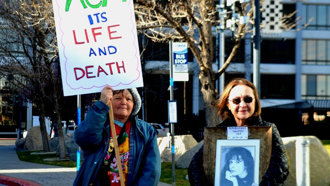 Marcella Salkowski, right, holds a framed photo of her daughter at a rally on Thursday outside the federal courthouse in Reno.