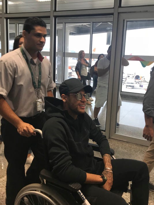 In this photo provided by Claire Dorland Clauzel, Brazilian soccer player Neymar is pushed in a wheelchair after arriving to the airport in Rio de Janeiro, Brazil, Thursday, March 1, 2018. Neymar will have surgery on a fractured toe in his right foot and could be out for up to three months, an estimate that would take the Brazil forward right up to the World Cup. Neymar was injured Sunday in Paris Saint-Germain's match against Marseille in the French league. (Claire Dorland Clauzel via AP)