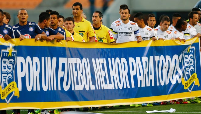 """Santos and Bahia soccer players hold a banner that reads in Portuguese; """"For a better soccer for all,"""" in protest during the Brazilian championship at the Pacaembu stadium, in Sao Paulo, Brazil."""