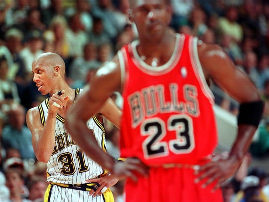 FILE - Pacers' Reggie Miller gestures toward the Bulls' Michael Jordan while talking to an official in the second half of their game at Market Square Arena May 23, 1998.