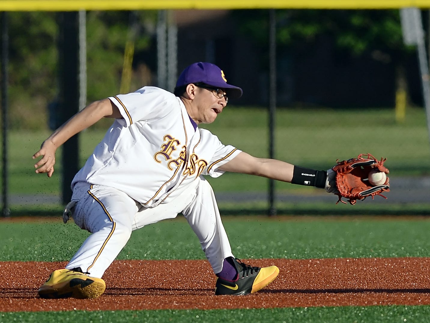 East High's Jose Gonzalez, left, reaches for the throw before tagging Monroe's Elis Rosado out at second during RCAC championship game played at Monroe Community College on Thursday, May 14, 2015.