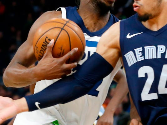 Minnesota Timberwolves' Andrew Wiggins, left, drives behind Memphis Grizzlies' Dillon Brooks in the first half of an NBA basketball game Monday, April 9, 2018, in Minneapolis. (AP Photo/Jim Mone)