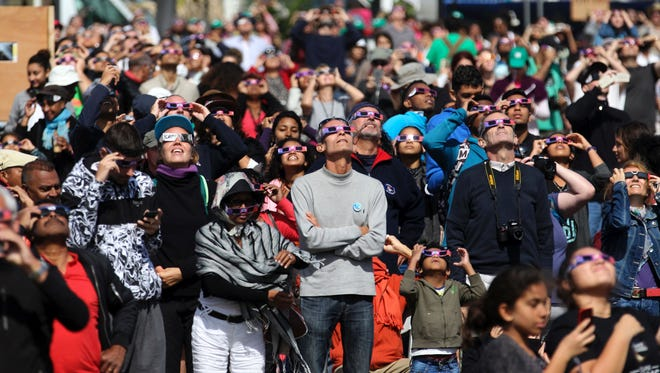 """People look through eclipse viewing glasses, telescopes and cameras during an annular solar eclipse, on Sept. 1, 2016, in Saint-Louis, on the Indian Ocean island of La Reunion. Stargazers in south and central Africa were treated to a spectacular solar eclipse on Sept. 1, 2016 when the Moon wanders into view to make the Sun appear as a """"ring of fire"""", astronomers say. The phenomenon, known as an annular solar eclipse, happens when there is a near-perfect alignment of the Earth, Moon and Sun. But unlike a total eclipse, when the Sun is blacked out, sometimes the Moon is too far from Earth, and its apparent diameter too small, for complete coverage."""
