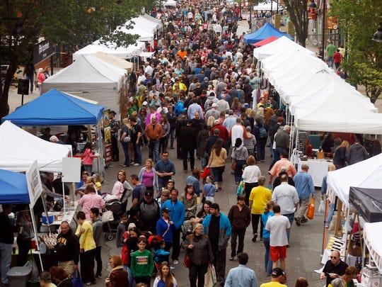 Visitors walk along Fourth Street Saturday, May 2,