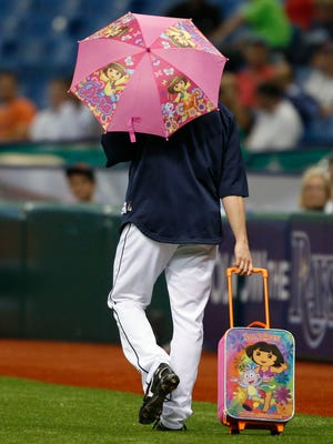 Tampa Bay Rays relief pitcher Brandon Gomes heads to the bullpen with a Dora The Explorer umbrella and rolling bag as part of rookie hazing.