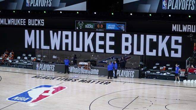 Officials stand beside an empty court at the scheduled start of an NBA playoff game between the Milwaukee Bucks and the Orlando Magic on Wednesday. The Bucks didn't take the floor in protest of racial injustice and the shooting of Jacob Blake in Kenosha, Wisconsin.
