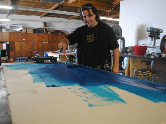 On Monday, Roger Floren dyes a sheet of wood which eventually will be used to create a layered replica of Lake Tahoe.