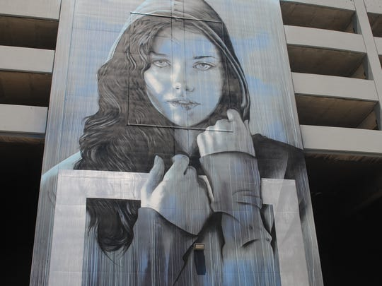 """Whitney Peak,"" also known as the ""Face of Reno,"" a mural by international muralist Christina Angelina, is featured on the ReTrac plaza parking lot building on Virginia Street."