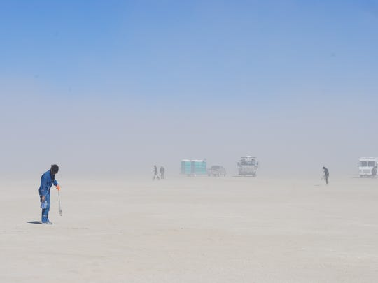 Thressa Barwood, a volunteer for the restoration crew that cleans up after Burning Man, picks up litter on Saturday, Oct. 1.