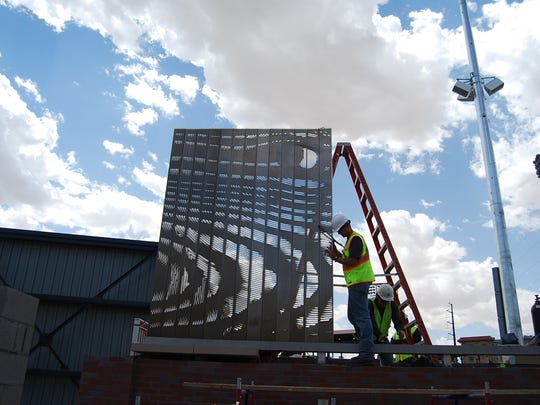 "Workers install the ""Not Whole Fence"" public art work at the Southwest University Park."