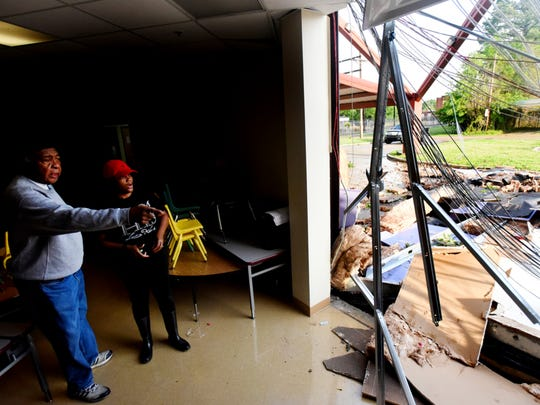 Director of the Galilee Learning Center Shemika Wright, left, and Galilee trustee James Carter inspect the storm damage to the Galilee Learning Center Saturday morning.
