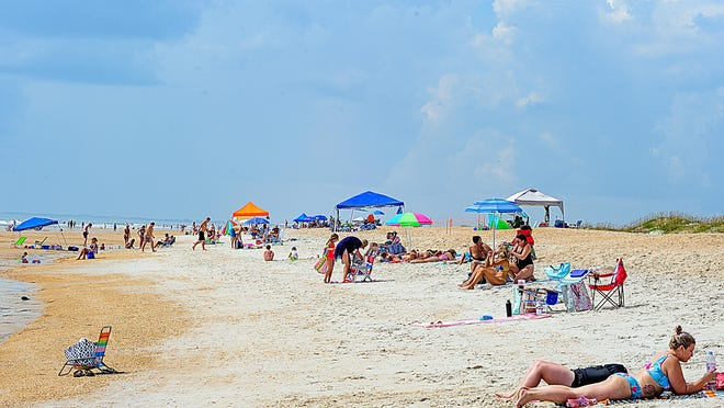 People send time on St. Augustine Beach on Friday. Despite the approaching hurricane, beach activity was typical of a summer day in the area.