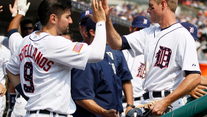 The Detroit Tigers' Josh Wilson, right, receives a high-five from Nick Castellanos (9) after scoring against the Toronto Blue Jays on a single by Ian Kinsler in a July 4 game last season in Detroit.