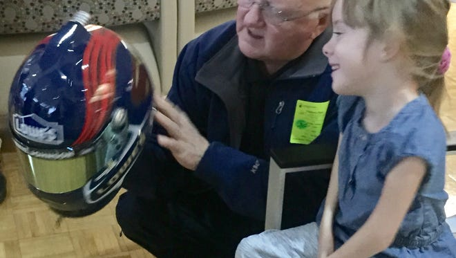 Walt Hollifield shows off one of the NASCAR helmet replica to Shriners patient Brayden Dame during the launch of the raffle fundraiser for the Vernon G. Hollifield Children's Charity.
