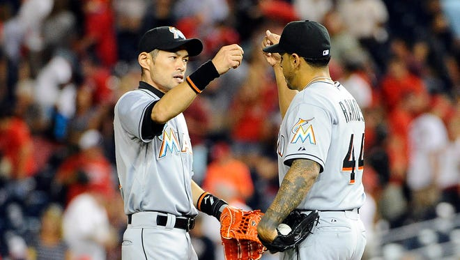 Miami Marlins relief pitcher A.J. Ramos (44) is congratulated by right fielder Ichiro Suzuki (51) after earning a save against the Washington Nationals at Nationals Park.