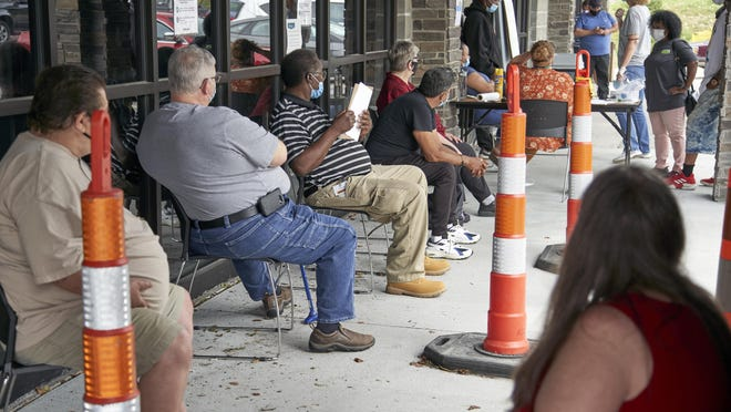 Job seekers exercise social distancing as they wait to be called into the Heartland Workforce Solutions office in Omaha, Neb., Wednesday, July 15, 2020. Nebraska reinstated job search requirements this week for most people claiming jobless benefits. Those unemployment insurance requirements were suspended in mid-March to help employees who had lost their jobs due to the coronavirus.
