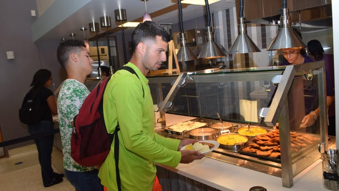 LSUA freshman business majors Alvaro Navarro (far left) and Gaven Stelly order food from the new Magnolia Café located in the Student Center on campus.
