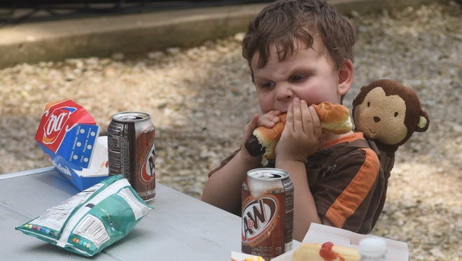 A Gassville in the Park attendee chows down on a hot dog during the 2019 event in this file photo.