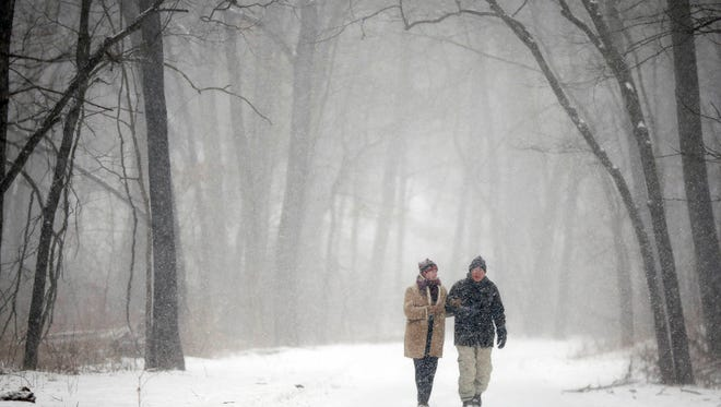 Mary Susan Gibson and her husband Richard walk down a section of trail near Ashworth Park as a light snow falls on Wednesday, Feb. 25, 2015, in Des Moines, Iowa.
