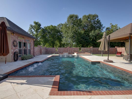 The beautiful pool and patio area offer lush landscaping