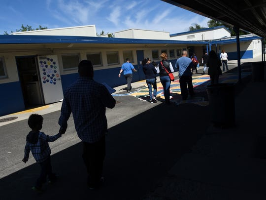 School officials, teachers and parents walk Booth Elementary School to find where they can squeeze in more students.