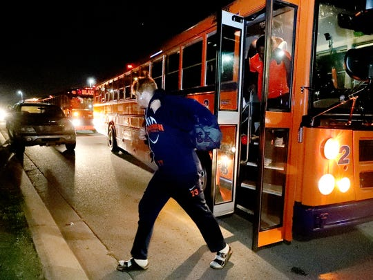 Blackman football players exit the buses with their gear after arriving back at Blackman High School early Saturday morning.