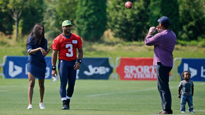 Seattle Seahawks quarterback Russell Wilson, second from left, watches as his girlfriend, entertainer Ciara Harris, left, plays catch with Wilson's brother Harrison Wilson IV, as he stands next to Harris' son Future, 1, Thursday, Aug. 13, 2015, following NFL football training camp in Renton, Wash.
