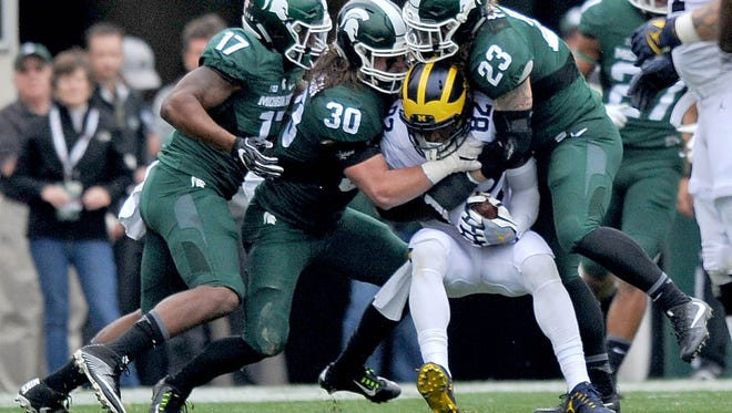 Spartan defenders Tyriq Thompson (17)_ Riley Bullough (30) and Chris Frey (23) gang tackle Amara Darboh (82).