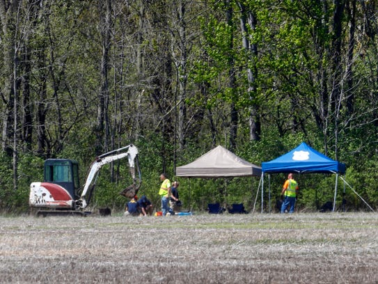 Authorities work along a rural wooded area in Macomb