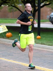 Dominic Reed takes first place with a time of 16:52 at the 2015 Dig'Em Dash 5K held Saturday morning in front of Kellogg Headquarters.