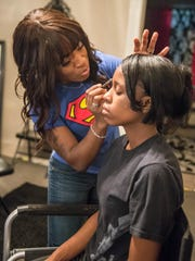 Ebony Roberson uses an eyebrow pencil on her client